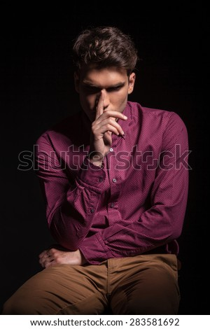 Young casual man sitting while holding one hand to his nose. - stock photo