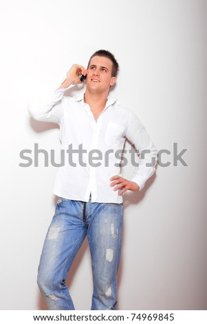 young casual man talking on the phone against wall - stock photo
