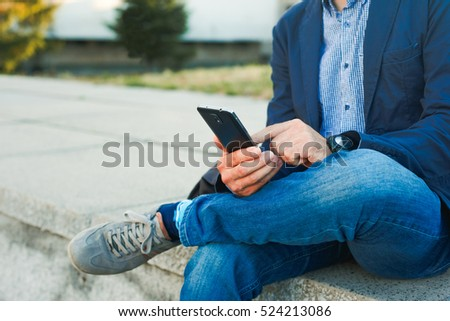 Young casual man using smart phone sitting outdoors