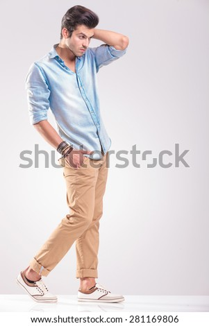 Young casual man walking on grey studio background fixing his hair while holding one hand in his pocket. - stock photo