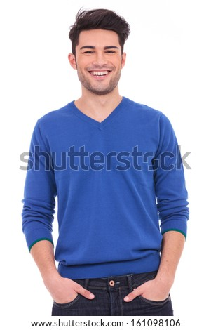 young casual man with hands in pockets smiling at the camera on white background - stock photo