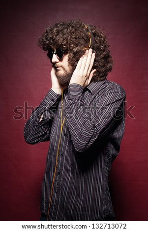 young casual man with long curly hair listening music with headphone on red background - stock photo