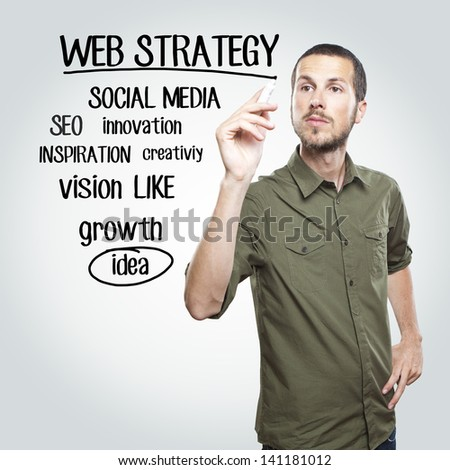 young casual man writing web strategy  diagram on glass board wi - stock photo