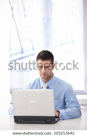 Young casual office worker working on laptop in bright office. - stock photo