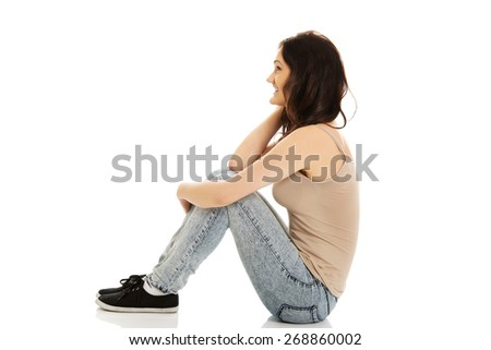 Young casual student woman sitting on the floor. - stock photo