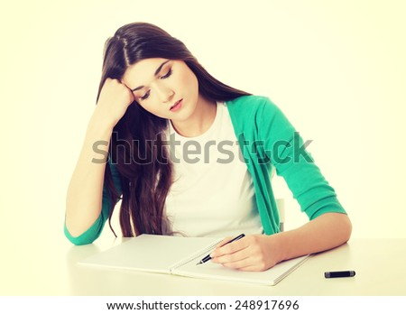 Young casual student woman writing in workbook.  - stock photo