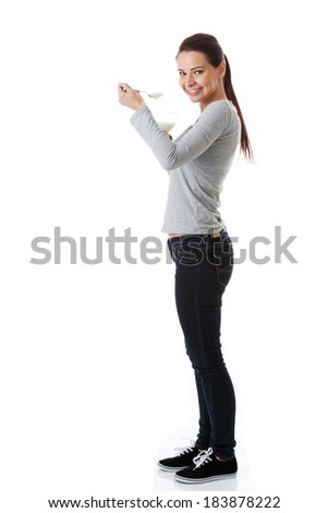 Young casual woman eating a yoghurt. Isolated on white. - stock photo