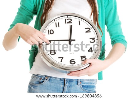 Young casual woman holding clock. Isolated on white.