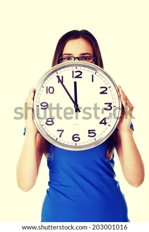 Young casual woman holding clock. Isolated on white. - stock photo