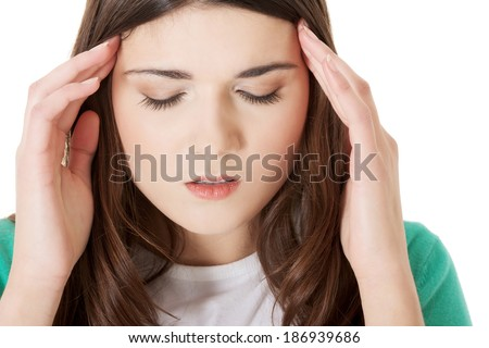 Young casual woman is having headache. Isolated on white. - stock photo