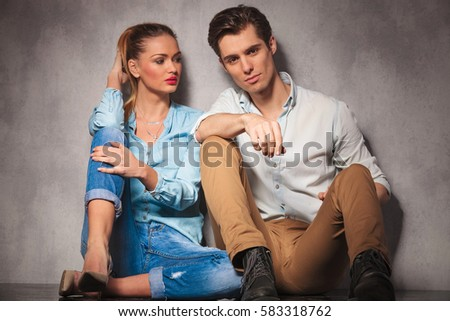 young casual woman looks at her boyfriend while sitting together on the floor in studio
