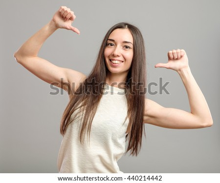 Young casual woman pointing at herself cheering happy isolated on gray background - stock photo