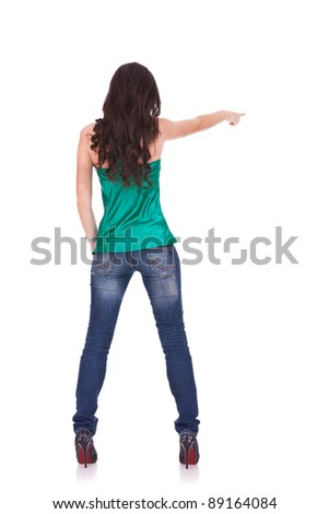 young casual woman points finger at something in her back. Isolated on white background - stock photo