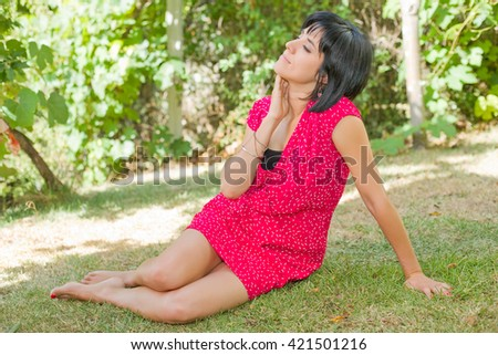 young casual woman posing seated, outdoors - stock photo