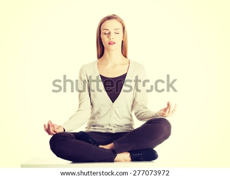 Young casual woman sitting and doing yoga - stock photo