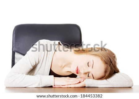 Young casual woman student is sleeping on a desk. Isolated on white.