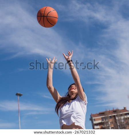 Young casual woman throwing basketball ball outdoors in a sunny day. - stock photo