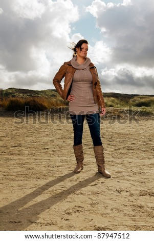 Young casual woman wearing jeans, woolen sweater and brown leather jacket standing on the beach with dunes in background. Hair blown by the wind. Cloudy sky.