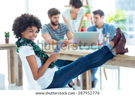 Young casual woman with feet on the table in the office - stock photo