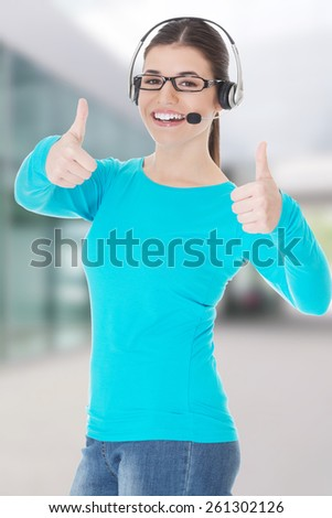 Young casual woman with headphones and microphone showing ok - stock photo