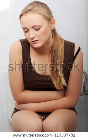 Young casual woman with stomach issues in toilet - stock photo