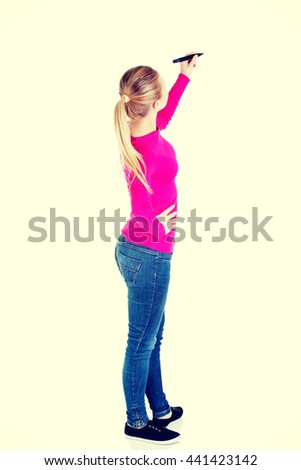 Young casual woman writing on copy space. - stock photo