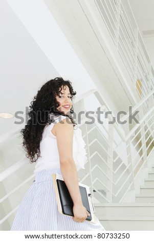 Young casually dressed business woman going upstairs - stock photo