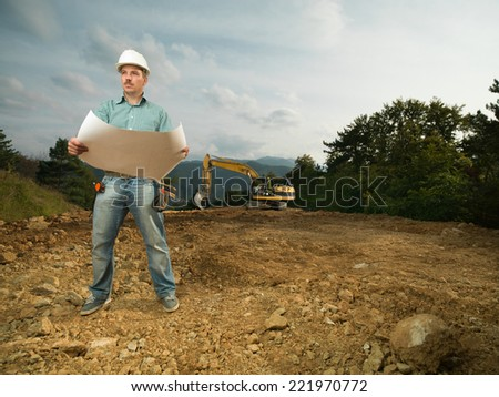 young caucasian architect standing on construction site holding blueprint