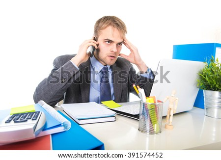 young Caucasian attractive businessman worried and tired talking on mobile phone sitting at laptop computer office desk working in stress overworked and frustrated isolated on white background - stock photo