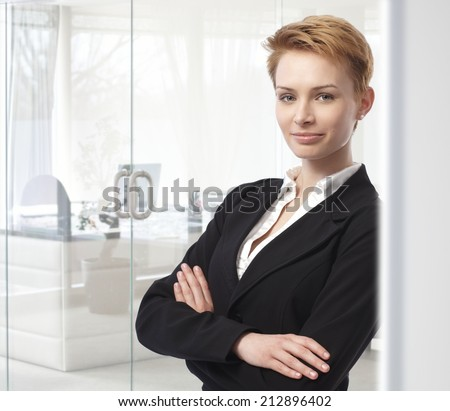 Young caucasian attractive businesswoman standing arms crossed at business office. Leaning against wall, looking at camera, smiling, confident, woman suit. Copyspace. - stock photo