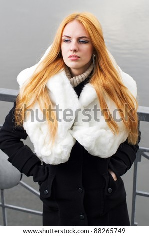 Young caucasian beautiful  redhead  woman against urban background.