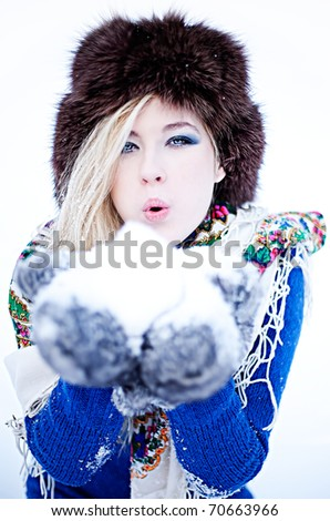 Young caucasian blonde wearing blue sweater, furry hat with gloves and traditional shawl blowing snow in winter scenery. - stock photo