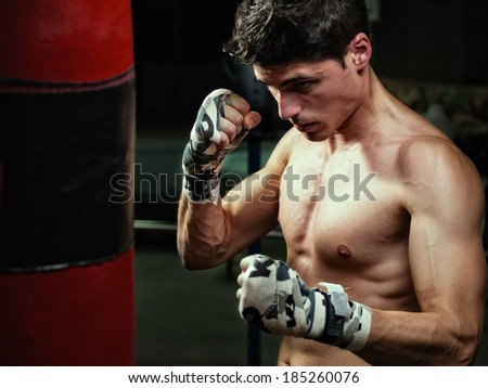 Young caucasian Boxer training with a punching bag in his home gym - stock photo
