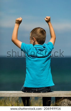 Young caucasian boy celebrating a victory. - stock photo