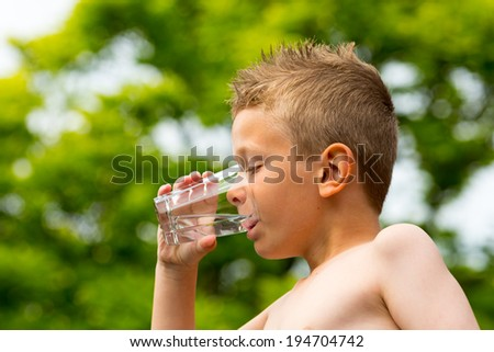 Young caucasian boy drinking from glass with fresh water outdoors during summer time.