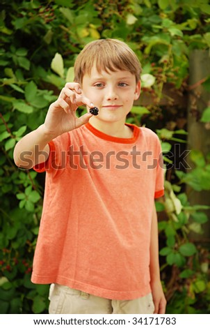 Young caucasian boy holding blackberry at farm