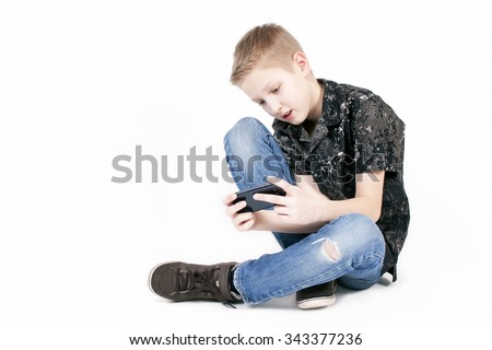 Young caucasian boy sittind on floor and browsing snapshots or video on a smart phone isolated on white background.