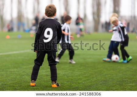 Young caucasian boys during a kids soccer training session on green turf. - stock photo