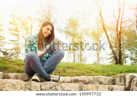 Young Caucasian brunette beautiful woman with tablet sitting on stairs in park wearing casual modern clothes. - stock photo