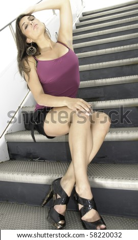 Young Caucasian brunette in summer attire and hoop earrings sits waiting on mobile stairs at airport - stock photo