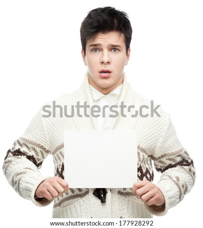 young caucasian brunette man in winter clothing holding sign and looking at camera with scared expression isolated on white - stock photo