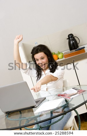 young caucasian brunette with a laptop at home with arms up.Concept of good news,success,online bidding