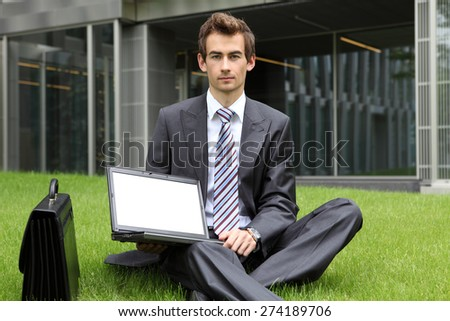 young caucasian businessman sitting on grass using his laptop