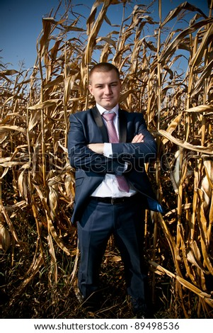 Young caucasian businessman standing in corn field - stock photo