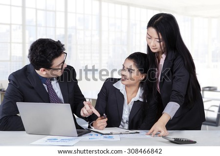 Young caucasian businessman talking a job with his partners in a meeting at office - stock photo