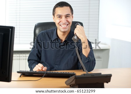 Young caucasian businessman talking on cell telephone and - stock photo