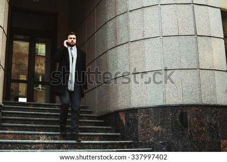 young caucasian businessman talking on phone near the business center