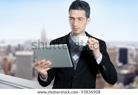 Young caucasian businessman with a cup of coffee uses a digital tablet on the roof of business center. Blurred cityscape with skyscrapers on background. - stock photo