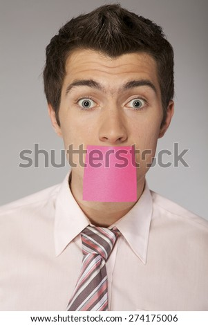 Young caucasian businessman with censorship card on his mounth - stock photo