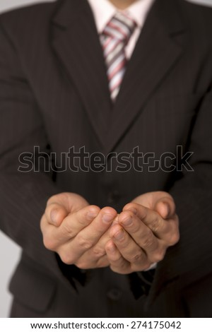 Young caucasian businessman with cupped hands - stock photo